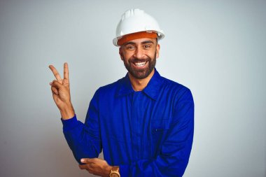 Handsome indian worker man wearing uniform and helmet over isolated white background smiling with happy face winking at the camera doing victory sign. Number two.