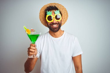 Indian man wearing summer funny look drinking cocktail over isolated white background with a happy face standing and smiling with a confident smile showing teeth