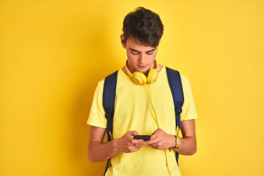 Teenager boy wearing headphones and using smartphone over isolated background with a confident expression on smart face thinking serious