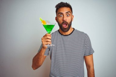 Young indian man drinking cocktail with alcohol standing over isolated white background scared in shock with a surprise face, afraid and excited with fear expression