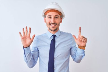 Young business man wearing contractor safety helmet over isolated background showing and pointing up with fingers number seven while smiling confident and happy.