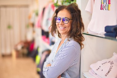 Middle age beautiful businesswoman wearing striped shirt and glasses smiling happy and confident leaning on the wall at clothes shop