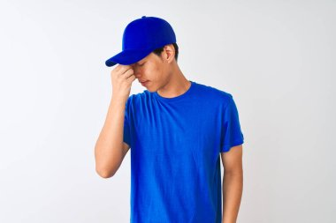 Chinese deliveryman wearing blue t-shirt and cap standing over isolated white background tired rubbing nose and eyes feeling fatigue and headache. Stress and frustration concept.