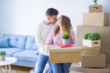 Young beautiful couple in love moving to new home, holding cardb