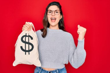 Young beautiful girl holding money bag with dollar symbol for business wealth over red background screaming proud and celebrating victory and success very excited, cheering emotion
