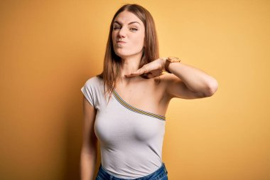 Young beautiful redhead woman wearing casual t-shirt over isolated yellow background cutting throat with hand as knife, threaten aggression with furious violence
