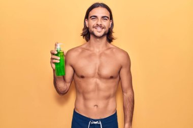 Young handsome man wearing swimwear holding aloe vera looking positive and happy standing and smiling with a confident smile showing teeth