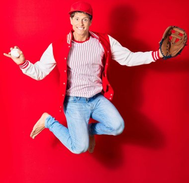 Young handsome man wearing sporty clothes smiling happy. Jumping with smile on face playing baseball using ball and glove over isolated red background