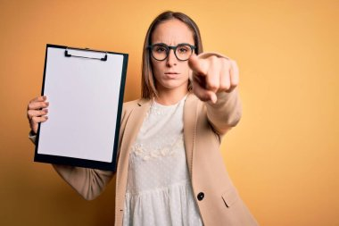 Beautiful inspector woman wearing glasses holding checklist clipboard over yellow background pointing with finger to the camera and to you, hand sign, positive and confident gesture from the front