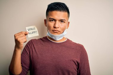 Young handsome latin man wearing medical mask holding paper with virus alert message with a confident expression on smart face thinking serious