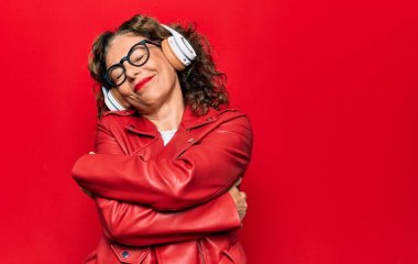 Middle age beautiful woman listening to music using headphones over red background hugging oneself happy and positive, smiling confident. Self love and self care