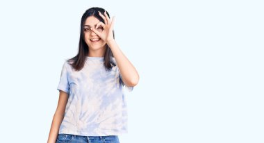 Young beautiful girl wearing casual t shirt doing ok gesture with hand smiling, eye looking through fingers with happy face.