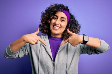 Beautiful curly arab sportswoman doing sport wearing sportswear over purple background looking confident with smile on face, pointing oneself with fingers proud and happy.