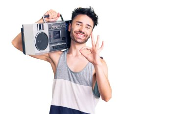 Young hispanic man holding boombox, listening to music doing ok sign with fingers, smiling friendly gesturing excellent symbol