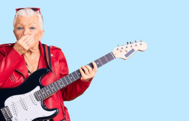 Senior beautiful woman with blue eyes and grey hair wearing a modern look playing electric guitar smelling something stinky and disgusting, intolerable smell, holding breath with fingers on nose. bad smell