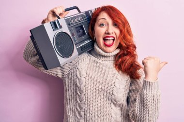 Beautiful redhead woman listening to music holding vintage boombox over pink background pointing thumb up to the side smiling happy with open mouth