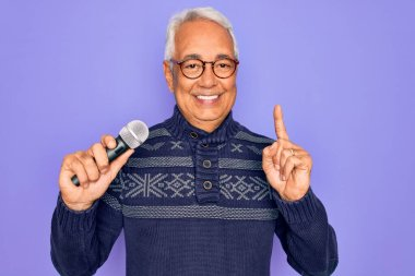Middle age senior grey-haired singer man singing using music microphone over purple background surprised with an idea or question pointing finger with happy face, number one
