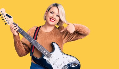 Young blonde plus size woman playing electric guitar pointing finger to one self smiling happy and proud