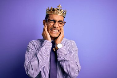 Young handsome african american man wearing golden crown of king over purple background covering ears with fingers with annoyed expression for the noise of loud music. Deaf concept.