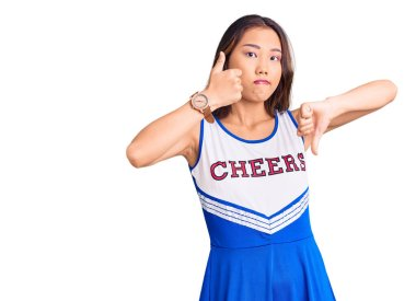 Young beautiful chinese girl wearing cheerleader uniform doing thumbs up and down, disagreement and agreement expression. crazy conflict