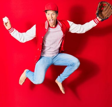 Young handsome man wearing sporty clothes. Jumping with open mouth playing baseball using ball and glove over isolated red background