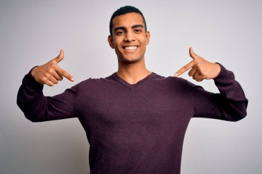 Young handsome african american man wearing casual sweater over white background looking confident with smile on face, pointing oneself with fingers proud and happy.