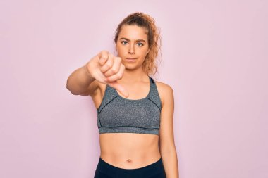 Young beautiful blonde sportswoman with blue eyes doing exercise wearing sportswear looking unhappy and angry showing rejection and negative with thumbs down gesture. Bad expression.