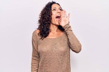 Middle age beautiful woman wearing casual sweater shouting and screaming loud to side with hand on mouth. communication concept.