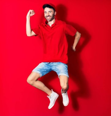Young handsome deliveryman wearing cap smiling happy. Jumping with smile on face over isolated red background