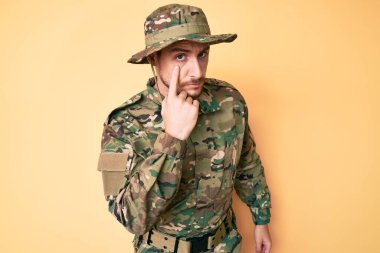 Young caucasian man wearing camouflage army uniform pointing to the eye watching you gesture, suspicious expression