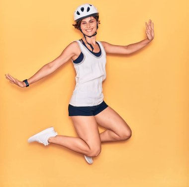 Young beautiful biker woman wearing bike helmet smiling happy. Jumping with smile on face and arms opened over isolated yellow background.