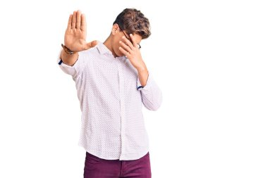 Young handsome man wearing business clothes and glasses covering eyes with hands and doing stop gesture with sad and fear expression. embarrassed and negative concept.