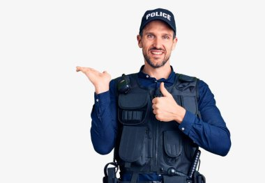 Young handsome man wearing police uniform showing palm hand and doing ok gesture with thumbs up, smiling happy and cheerful