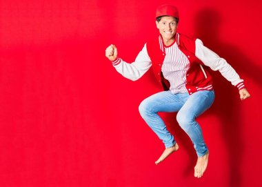 Young handsome man wearing baseball clothes smiling happy. Jumping with smile on face over isolated red background