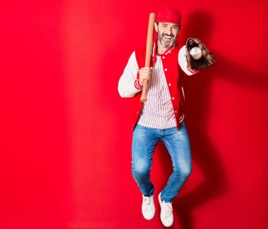 Middle age handsome man wearing sporty clothes smiling happy. Jumping with smile on face playing baseball using bat ,ball and glove over isolated red background