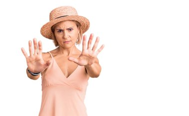 Young blonde woman wearing summer hat doing stop gesture with hands palms, angry and frustration expression