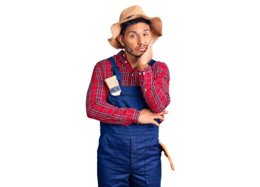 Handsome latin american young man weaing handyman uniform thinking looking tired and bored with depression problems with crossed arms.