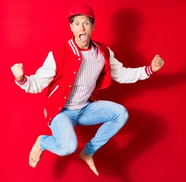 Young handsome man wearing baseball clothes. Jumping with open mouth doing winner sign with fists up over isolated red background