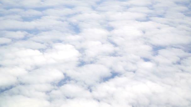 pohled z letadla na bílý načechraný mraky ve vzduchu