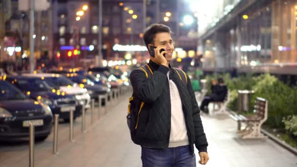 Young Man Speaking by Phone in the evening city street with bokeh light effect.