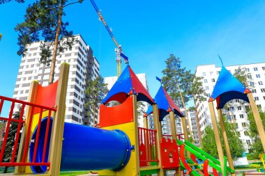 multi-colored playground for children in the park between high-rise buildings