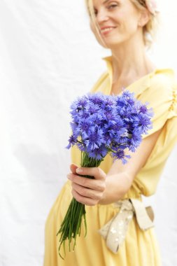 Romantic bouquet of blue flowers of cornflowers in the hands of a woman on white background. blurs effect