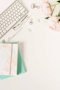 Flat lay women's office desk. Female workspace with flowers peonies, accessories, notebook, glasses on white background. Top view feminine background.Copy space