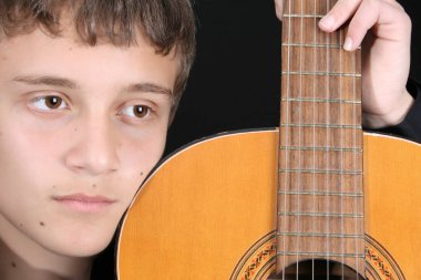 Close up of teen boy with his guitar