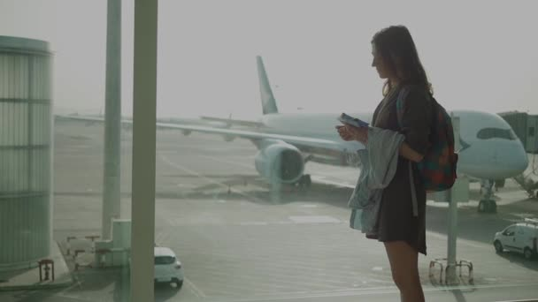 Waiting for flight - a woman with tickets at the airport terminal