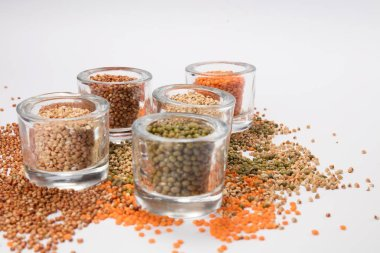 top view of a different beans and seeds near in a glass jar on a white background