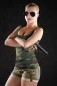 sexy Mädchen mit militärischem Stil posiert mit Waffen und Sonnenbrille isoliert im Studio