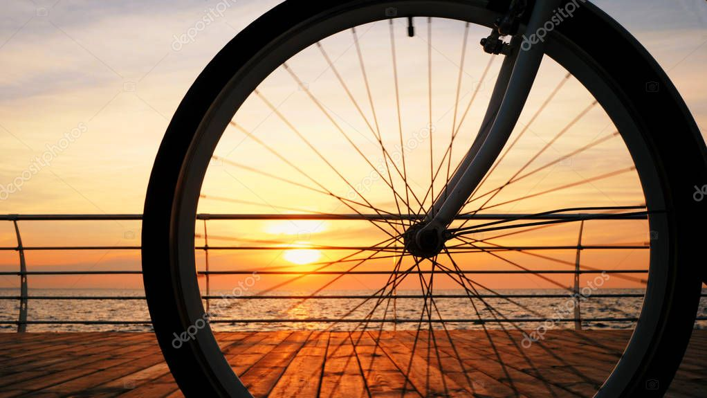 Spinning bicycle wheel against amazing sunrise and sea. Close up bike truck rotating with sky background