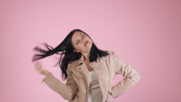 Closeup Beauty portrait of brunette pretty caucasian woman in fashion jacket on pink background in studio. Girl preen near camera.
