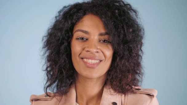 Young african american woman posing over blue background. Trendy and urban style. Afro curly hair, snow-white smile, healthy lifestyle. Slow motion